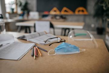 A classroom desk with school supplies and a mask