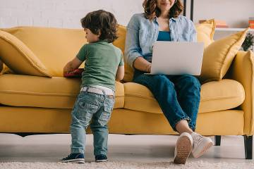 Child standing next to mother sitting on couch working on a laptop