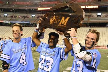 Hopkins players hoist the rivalry trophy after a win against Maryland