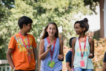 Three smiling adolescents wearing CTY lanyards