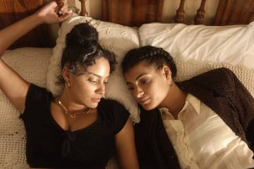 A still from De Lo Mio portrays two sisters laying on a bed