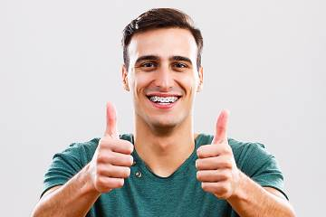 Smiling man wearing braces on his teeth gives two thumbs up