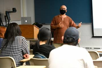An instructor speaks with students in a classroom