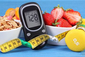 Glucose monitor, measuring tape, and a bowl of strawberries