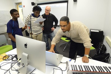 Thomas Dolby works with two young male singers at microphones while another man mixes sound on a laptop computer