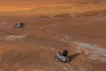 Two drone devices with multiple rotors fly across a brown, rocky, barren surface, representing the surface of Titan