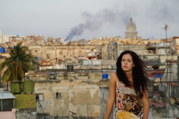 A woman sits on a rooftop while Havana sprawls out behind her