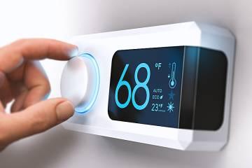 Woman's hand adjusting an indoor thermostat
