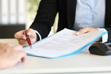 An attorney indicates to client where he should sign a document.