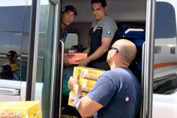 Two men stand inside an airplane and unload boxes of Cheerios and power bars to two people waiting outside the plane