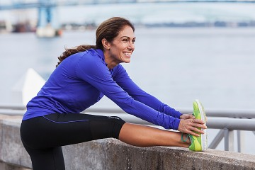 Woman in athletic gear stretches her leg on a wall overlooking a body of water.