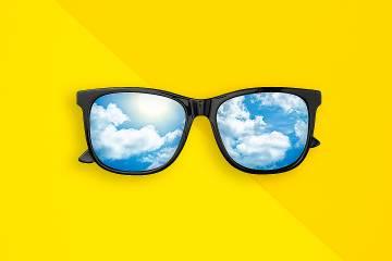 Illustration of large-framed glasses with lenses reflecting clouds