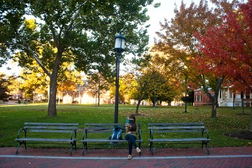 A female student reads a book on a campus quad bench in fall