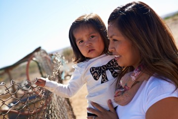 A close up image of a mother holding her toddler daughter up to a chain link fence