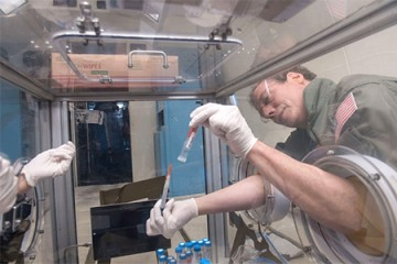 Andy Feinberg works with pipette aboard NASA's zero-gravity aircraft