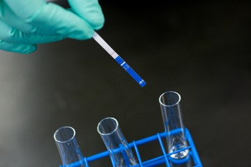 A gloved hand tests fentanyl strips