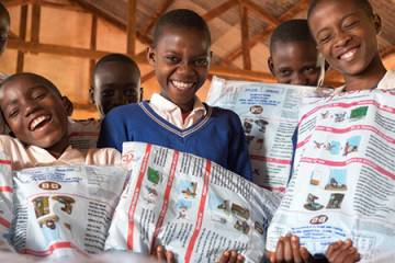 Schoolchildren receive free bed nets during a distribution in Tanzania.
