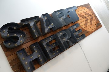 'Start Here' sign on wood background