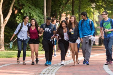 Seven students walk along the quad, arm in arm
