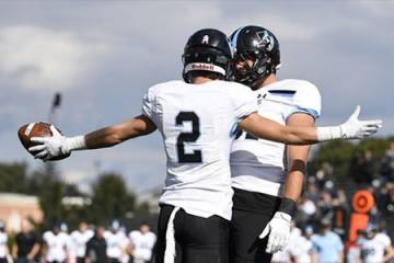 Two Johns Hopkins football players celebrate a touchdown