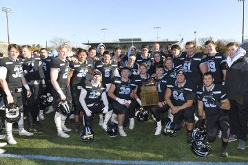 Football team poses with trophy