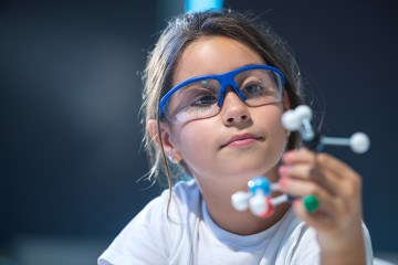 A little girl wearing safety goggles inspects a model of a molecule