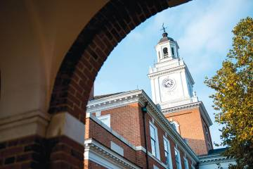 Gilman Hall clock tower as seen from beneath brick archway