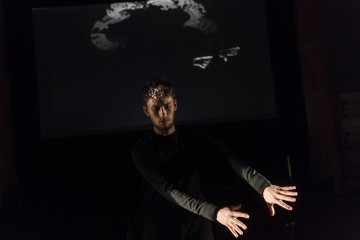 A man in front of a black screen waves his hand in front of a light while smokey swirls are projected on a screen behind him