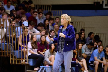 Neuroscientist Linda Gorman holds a microphone and addresses a gym full of undergraduate students