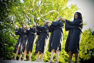 Graduates in caps and gowns spray champagne