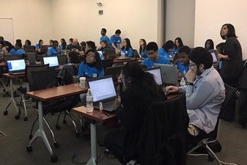Students sit in a classroom and look at computer screens
