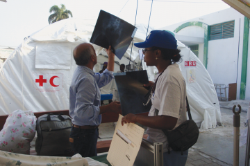 Emergency personnel review X-rays without electric viewing screens at Haiti's University Hospital one month after the earthquake