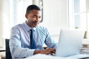 Man in office looking at laptop screen