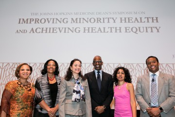 Six panelists at the Dean's Symposium pose for a photo in front of a screen with the talk title