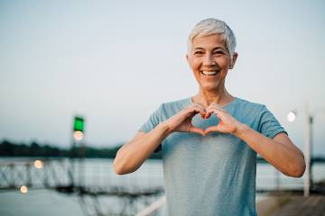 Active older woman making a heart with her hands