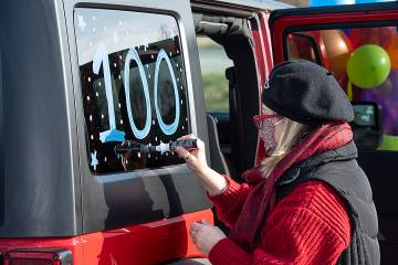 Woman painting 100 on car window