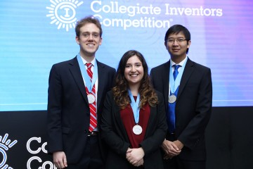 Three Hopkins team members pose with silver medals