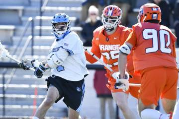 Hopkins lacrosse player winds up for a shot against two Syracuse defenders