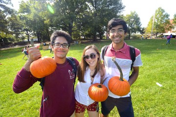 Three students pose for a photo while holding pumpkins