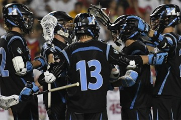 Hopkins lacrosse players in black uniforms with blue numbers