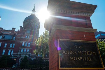 The Johns Hopkins Hospital sign and dome with brightly shining sun