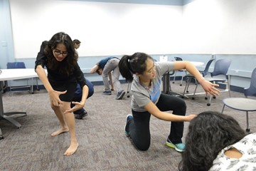 Students contort their bodies into unusual positions during an improv exercise