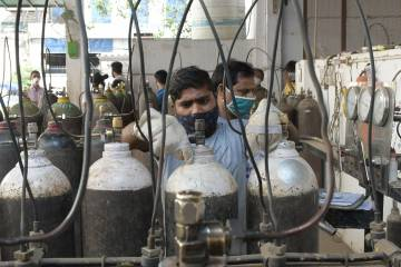 A man in a mask fills oxygen tanks