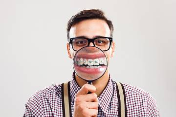 Man wearing eyeglasses and also braces on his teeth