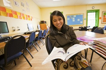 Student participating in Community Impact Internships program sits in a classroom with an open book