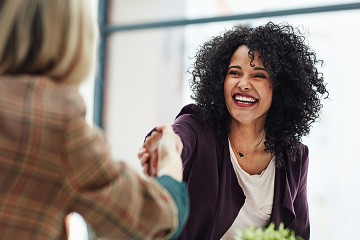 Smiling job applicant shakes hands with her interviewer
