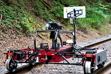 The robot spans across railroad tracks on a metal frame and is equipped with cameras and sensors