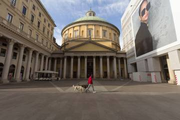 A person walks dogs in front of the Cathedral of San Carlo al Corso, Milan, Italy