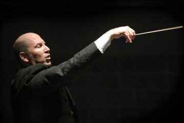 Jed Gaylin holds a baton mid-conducting