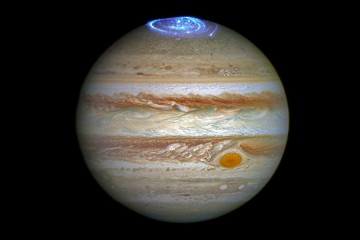 Image depicts a photo of Jupiter, striated with red and gray storm clouds and the iconic Red Dot, topped with an electric blue swirl of color on the north pole representing an aurora